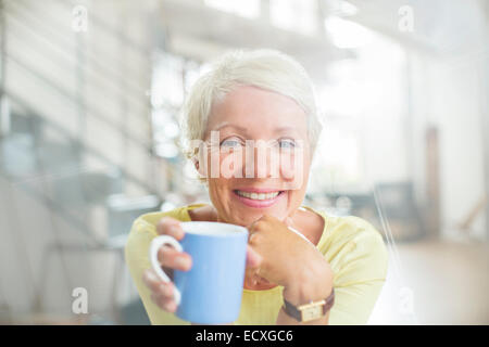 Older woman drinking cup of coffee - Stock Photo
