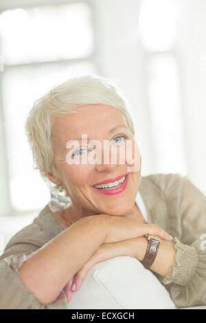 Older woman smiling on sofa - Stock Photo