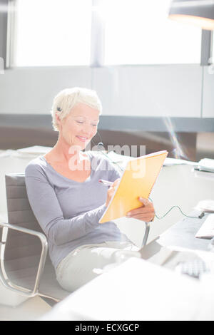 Businesswoman in headset writing in notebook at office desk - Stock Photo