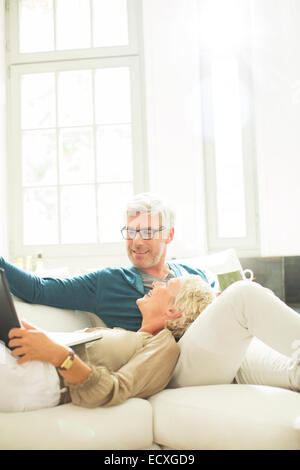 Older couple relaxing together on living room sofa - Stock Photo