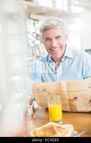 Older man reading newspaper at breakfast table