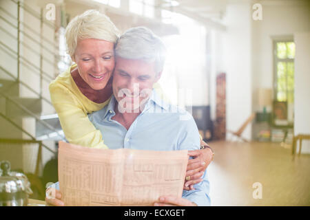Older woman hugging husband reading newspaper - Stock Photo