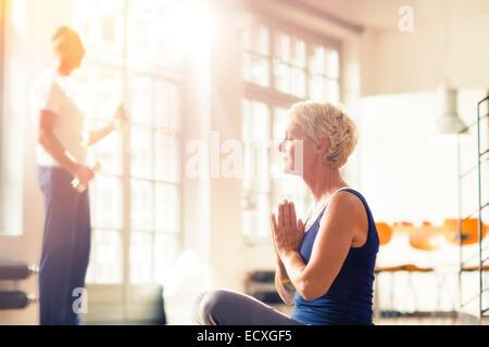 Older woman meditating on floor - Stock Photo
