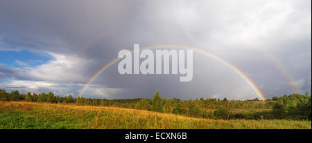 A bright double rainbow arches over a village field. - Stock Photo