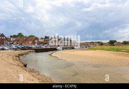 Boats moored and waterfront by a creek in the harbour at low tide in Blakeney, coastal north Norfolk, UK - Stock Photo