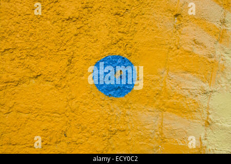 A Painted Yellow Brick Wall With A Blue Trimmed Window And A Green ...
