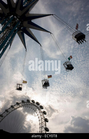 Rising circular fairground ride with EU member flags and Millennium (ferris) Wheel on London's Southbank. - Stock Photo