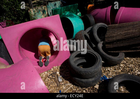 Boy climbs through tunnels in risk averse playground called The Land on Plas Madoc Estate, Ruabon, Wrexham, Wales. - Stock Photo