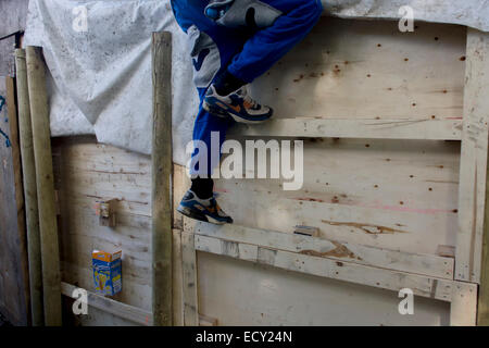 Boy climbs up wall in risk averse playground called The Land on Plas Madoc Estate, Ruabon, Wrexham, Wales. - Stock Photo