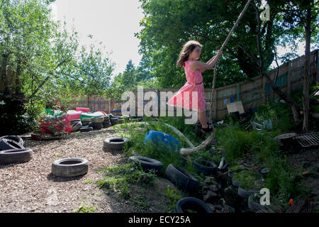 Girl swings on rope swing in risk averse playground called The Land on Plas Madoc Estate, Ruabon, Wrexham, Wales. - Stock Photo