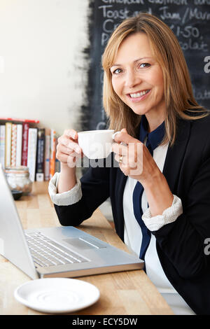 Businesswoman Using Laptop In Cafe - Stock Photo