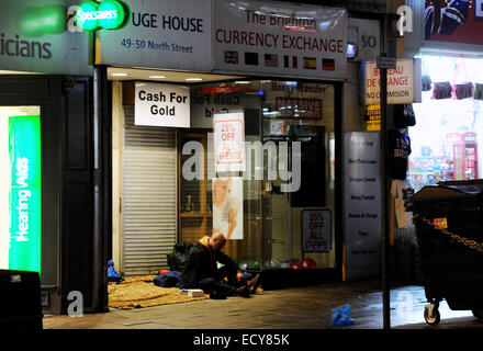 Brighton UK 21 December 2014 - Homeless man preparing to sleep rough in a doorway in North Street Brighton for the - Stock Photo