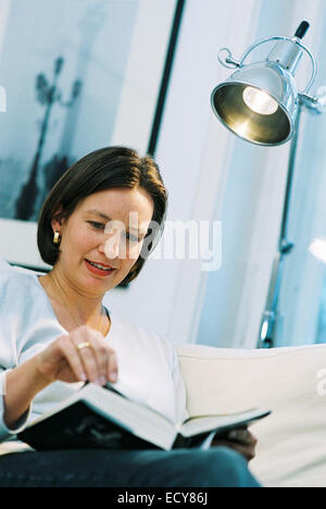 Middle-aged woman enjoys reading a book - Stock Photo