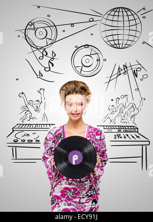 Colorful photo of a clubbing fashionable hippie deejay at the dancing party holding a retro vinyl record in her - Stock Photo