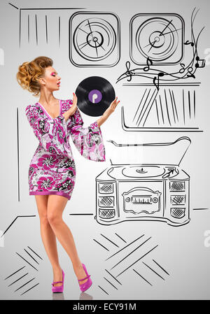 Colorful photo of a fashionable hippie homemaker holding a purple LP microgroove vinyl record in her hands on grey - Stock Photo