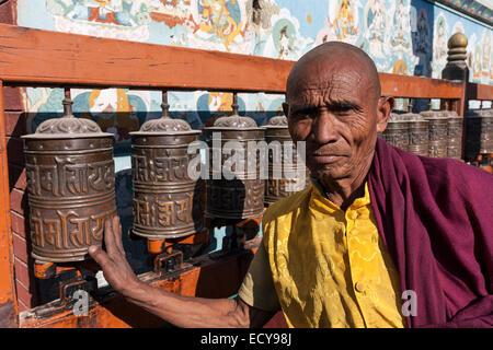 Monk turning prayer wheels, Boudhanath Stupa, Kathmandu, Nepal - Stock Photo