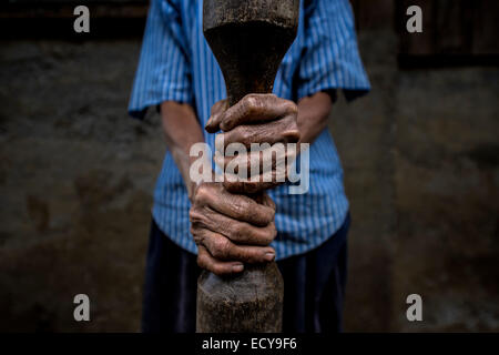 Woman holding bar for rice pounding, North Luzon, Philippines - Stock Photo