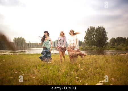 Caucasian women walking in field near lake