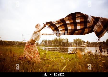 Caucasian woman spreading blanket in field