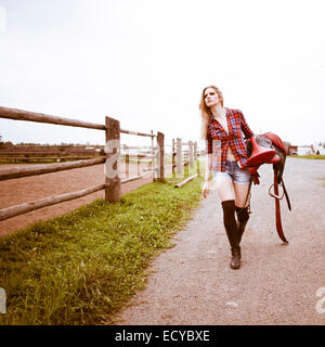 Caucasian woman carrying horse saddle on ranch - Stock Photo