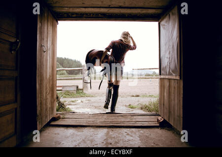 Caucasian woman carrying horse saddle in barn doorway - Stock Photo
