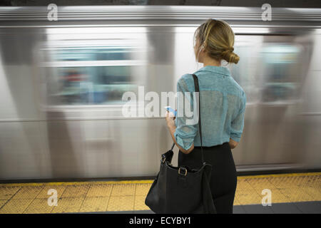 Caucasian woman standing near passing subway in train station - Stock Photo