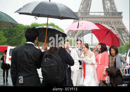 PARIS, FRANCE - MAY 19, 2013: Asian bride and groom holding umbrellas pose for photographs in front of the Eiffel - Stock Photo