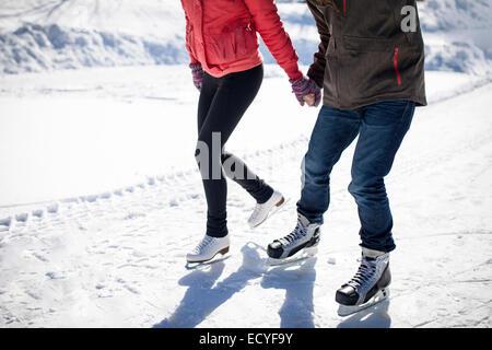 Caucasian couple ice skating on snowy frozen lake - Stock Photo