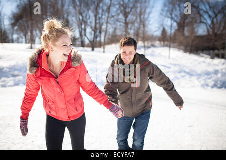 Caucasian couple ice skating on frozen lake - Stock Photo