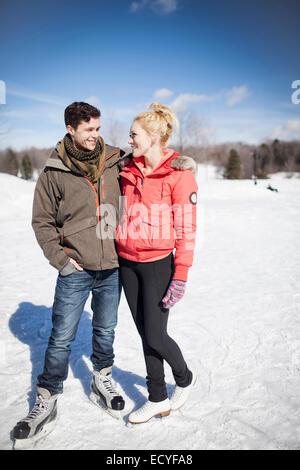 Caucasian couple ice skating on frozen lake - Stock Photo