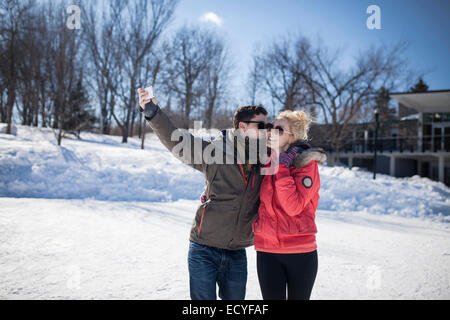 Caucasian couple taking cell phone selfie in winter - Stock Photo