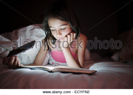 Mixed race girl reading by cell phone light in bed - Stock Photo