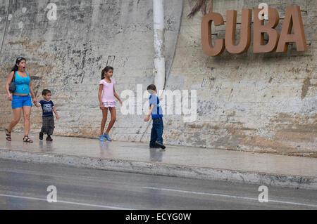 HAVANA, CUBA - JUNE 12, 2011: Young Cubans walk on sidewalk dominated by Cuba sign in La Rampa neighborhood. - Stock Photo