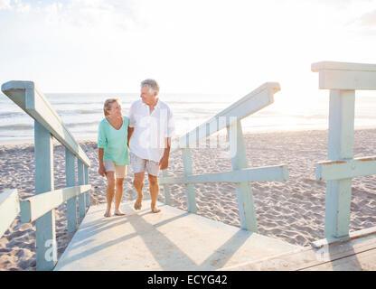 Caucasian couple walking on wooden boardwalk on beach