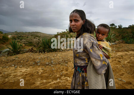 Tigrayan girl with baby and typical Ethiopian orthodox tattoos on forehead, Ethiopia - Stock Photo