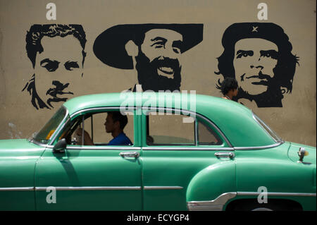 HAVANA, CUBA - JUNE 13, 2011: Classic American car drives past stencil billboard featuring Mella, Cienfuego, and - Stock Photo