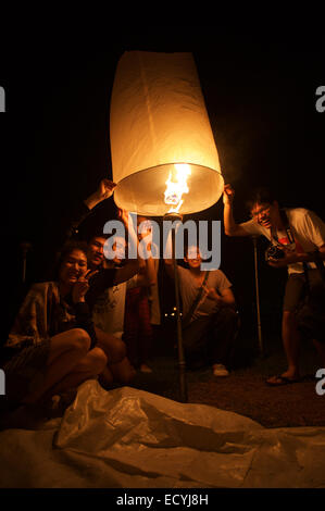 CHIANG MAI, THAILAND - OCTOBER 25, 2014: Group of young Thai people launch a sky lantern on the night of the Yi - Stock Photo