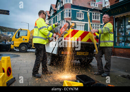 A two-man crew of Ceredigion County Council local authority direct labour workers wearing hi-vis yellow jackets - Stock Photo