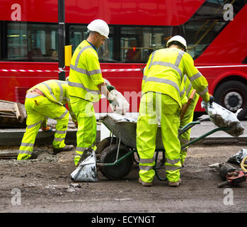 LONDON - OCTOBER 18TH: Unidentified workman preparing a mixture on October 18th, 2014 in London, England, UK. The - Stock Photo