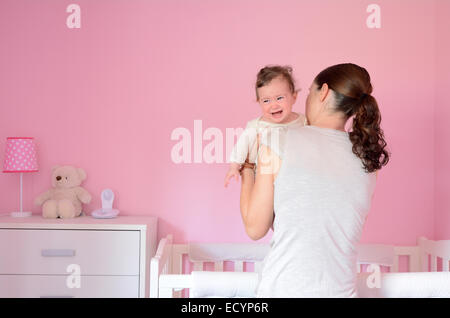 Young mother puts her baby (girl age 06 months) to sleep while she cries. Concept photo parenthood and motherhood. - Stock Photo
