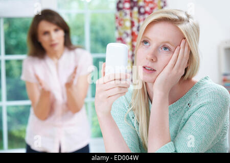 Mother Arguing With Teenage Daughter Over Use Of Mobile Phone - Stock Photo