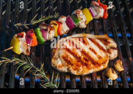 Pork steak and kebabs cooking on a barbecue grill - Stock Photo