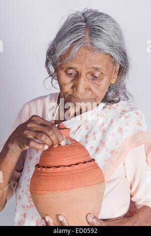 1 indian Old Senior Woman Saving money Piggy Bank - Stock Photo