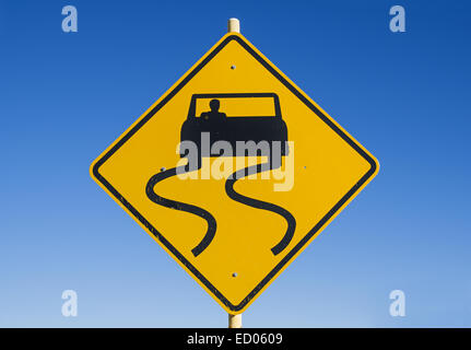 yellow and black caution slippery road sign with car and skid marks with blue sky background - Stock Photo