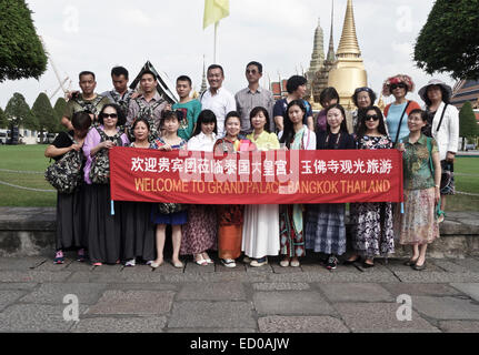 Group of Chinese tourists posing at the Outer court king's grand palace, Wat Phra Kaew, Bangkok, Thailand. - Stock Photo