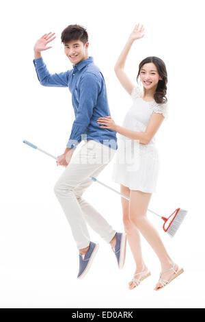 Happy young couple flying on broom - Stock Photo