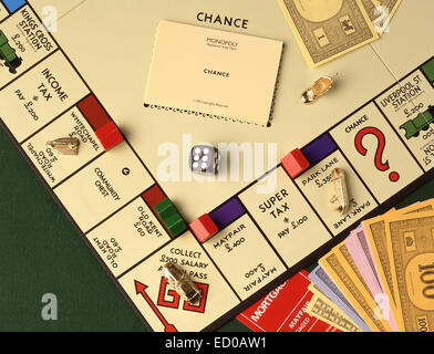 Monopoly board game with money, notes, counters and dice in studio setting - Stock Photo