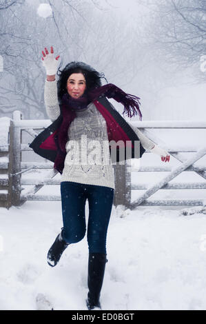 Woman throwing snowball - Stock Photo