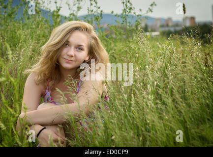 Portrait of teenage girl (14-15) sitting in field - Stock Photo