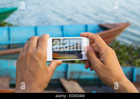 Man taking photo of boats on a lake, Phewa Lake, Pokhara, Nepal - Stock Photo